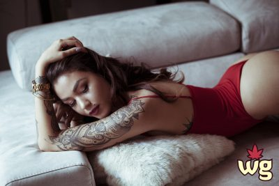 Hot tattooed woman posses in red bodysuit | Weed girls