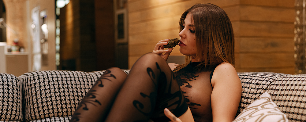 hot model smelling cannabis bud wearing a bodysuit and pantyhose
